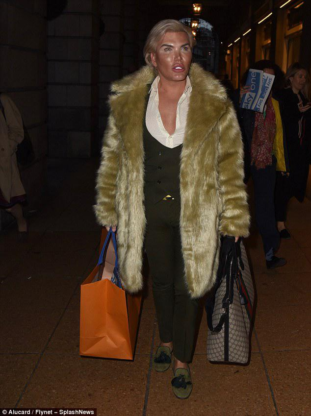Having fun: He proved to be in high spirits as he took to the streets of London, flashing his porcelain pearly whites as he grabbed onto bags full of purchases