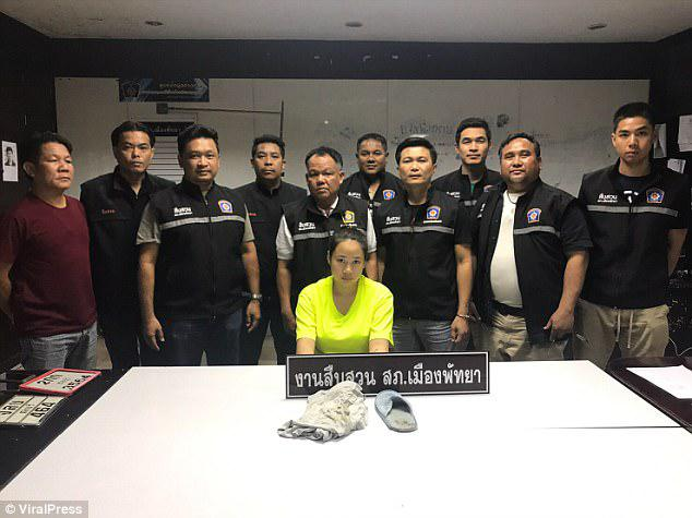 Netchanok Nokyungtong poses with local police in front of evidence used against her