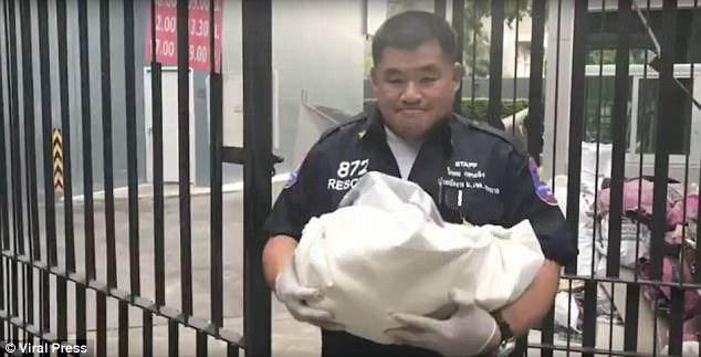 Tragic: A police officer carried the dead body of the newborn boy