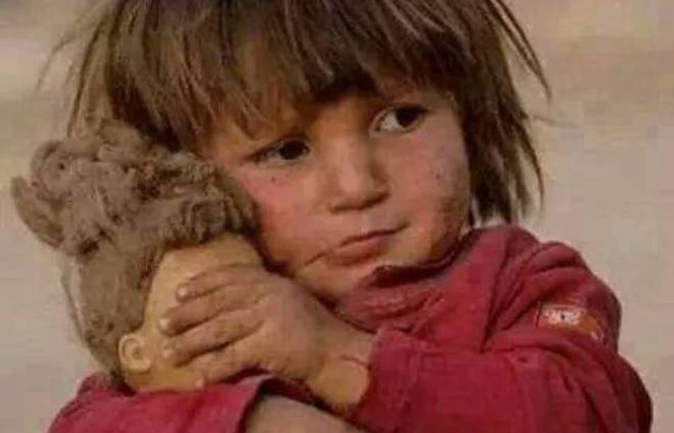 Συρία….Κ0ριτσάκι κρατάει τα μάτια της κούκλας του κλειστά να μην βλέπει τη φρίκη