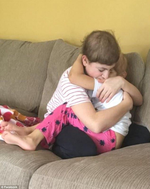 Jacob, 14, and his five-year-old sister hug as they both battle cancer. Their family had been told Jacob might not make it much longer when this photo was taken