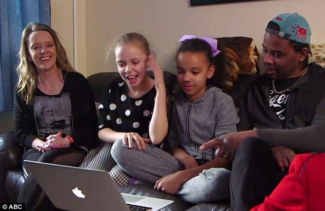 The girls wedged in between their parents Amanda Wanklin, left, and Michael Biggs, right on Good Morning America reacting to their National Geographic cover displayed on the laptop