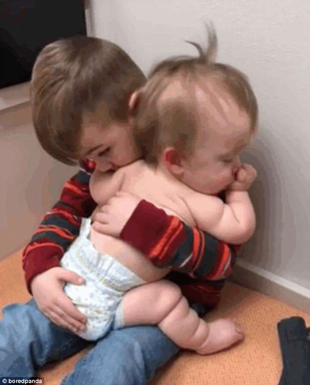 A baby girl looks very comfortable as her big brother rocks her to sleep