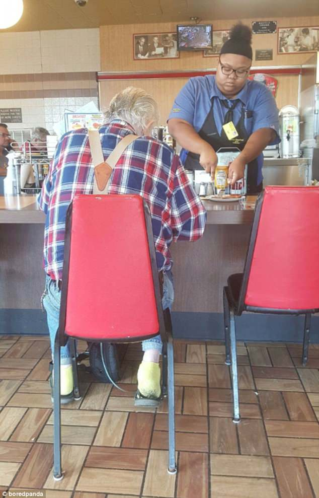 A waitress helps cut up an elderly man's breakfast at the restaurant she works at after losing the use of his hands
