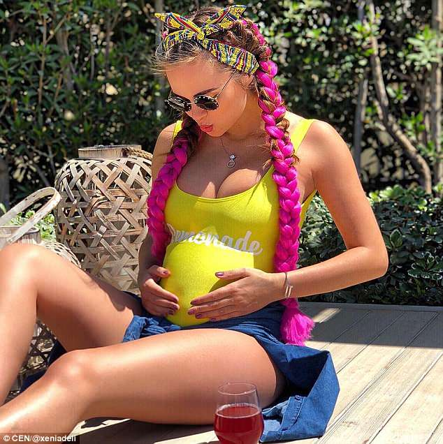 Xenia Deli, 28, is expecting her first child with her billionaire husband, posting this snapof her bulging belly under a yellow top and holding her stomach to Instagram
