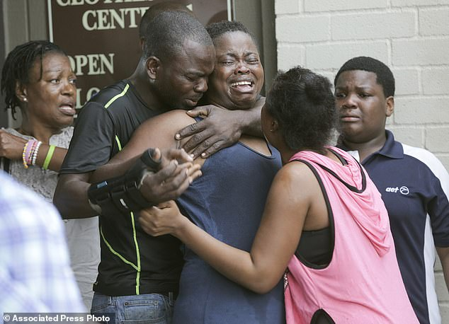 Sabine Ntongo is comforted by family after she found the bodies of her two young children