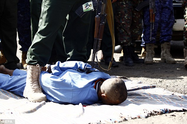 One of the rapists is pinned to the floor as a policeman stands over him with a gun before firing