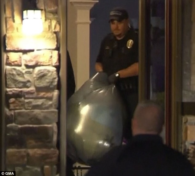 Police remove bags of evidence from the family's home on Wednesday night