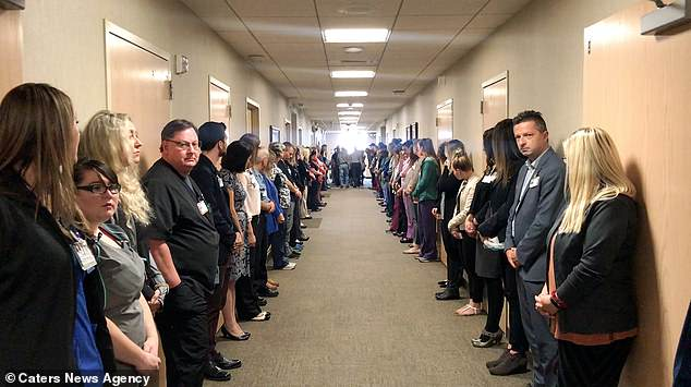 Dozens of staff lined the corridor and some appeared emotional as the terminally ill man was wheeled past in his final moments