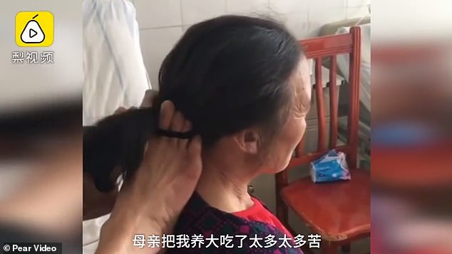 He also helps his mother brush her teeth, wash her face and tie her hair (pictured) daily