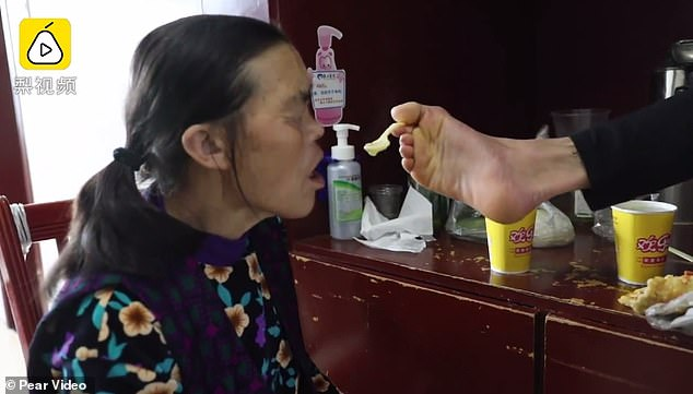Chen Cifang, 29, uses holds a spoon with his foot and feeds food into his mother's mouth