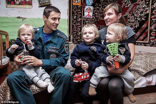Natalia Vorobyeva (right) with her three children (from left) Sasha, Danil, and Denis and fireman Aleksandr Mordvov. The three young boys died in a house fire in Russia