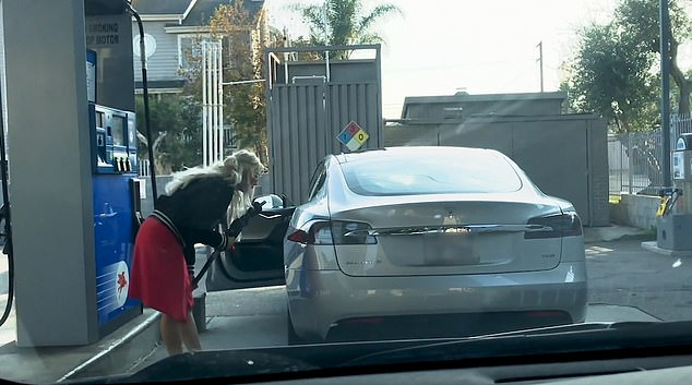 The woman is flummoxed by the fact that the Telsa car doesn't have a fuel nozzle
