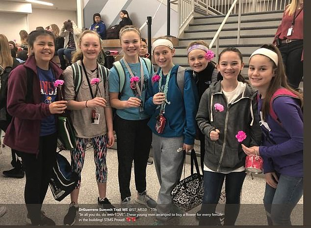 Students at Summit Trail Middle School in Kansas pose with their flowers on Valentine's Day